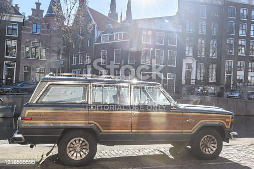Jeep Grand Wagoneer parked next to a canal in Amsterdam during a springtime morning. The Jeep Wagoneer/Grand Wagoneer was the longest produced Jeep vehicle and was produced from 1963-1991.