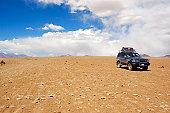 Black jeep driving in desert, Altiplano, Bolivia