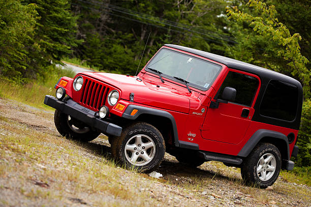 Jeep Wrangler TJ sitting on muddy dirt and gravel trail stock photo