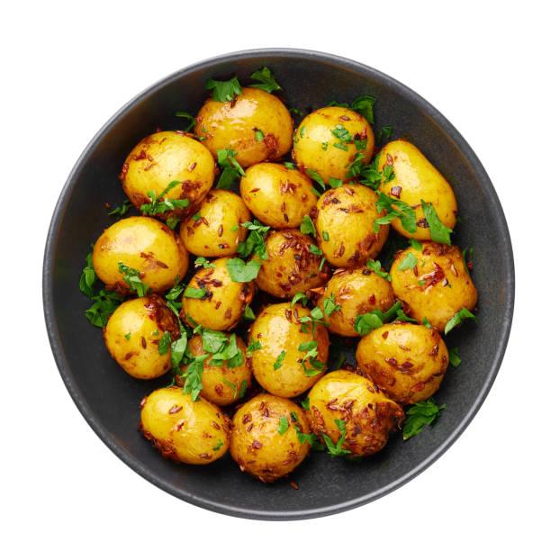 jeera aloo in schwarzer schale isoliert auf weißem hintergrund. jeera aloo ist indische küche gericht mit babykartoffeln, jeera samen und koriander. isolieren. ansicht von oben - salzkartoffel stock-fotos und bilder