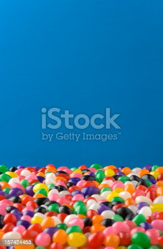 Jellybeans fill the lower 1/3 of the frame, Jellybeans in front are out of focus, those in back are in focus. Clipping Path around Jellybeans so the blue can be removed or changed.