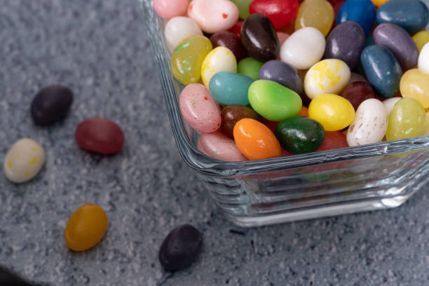Jelly beans spilling on blue stock photo