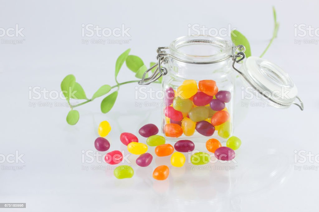 Jelly Beans Spilt From Glass Jar With Open Lid And Metal