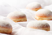Jelly filled doughnuts with powdered sugar on a bed
