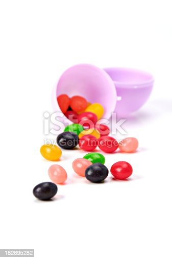 Multi-colored jellybeans in a purple Easter egg isolated on white.