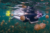 Woman swimming at the Jellyfish Lake or Ongeim'l Tketau as it is called in Palauan, is one of approximately 70 marine lakes scattered throughout the stunning limestone Rock Islands of the southern portion of the main Palau archipelago.