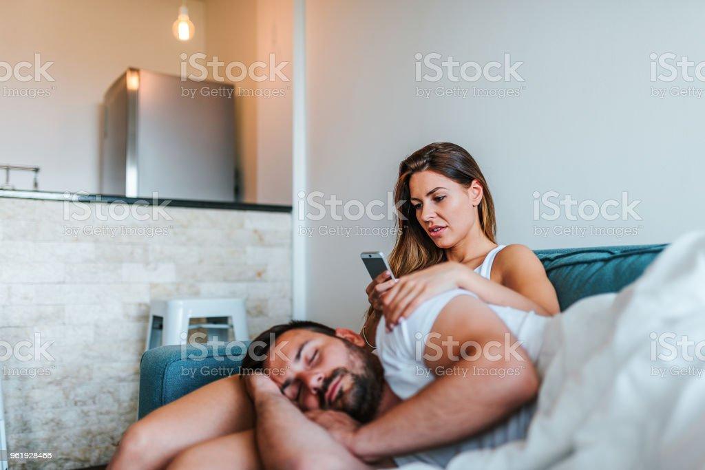 Jelous junge Frau Cheking Freund das Telefon, während er schläft. – Foto