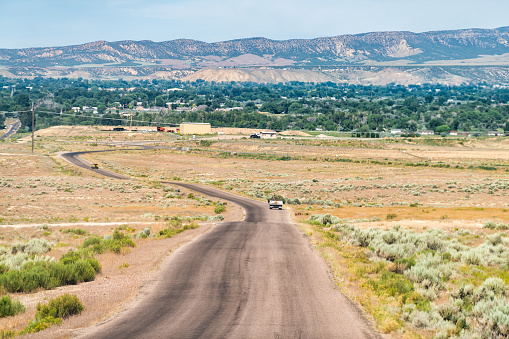 Jensen or Vernal Utah road highway with view of city near Dinosaur National Monument desert landscape