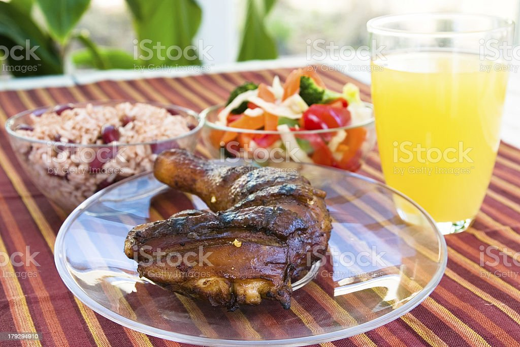 "Jerk Chicken with Vegetables, Rice and Lemonade ""Barbecued chicken leg also known as Jerk Chicken - Caribbean style served with vegetables, rice and lemonade.  Shallow DOF."" Barbecue - Meal Stock Photo"