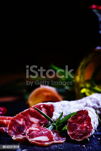 Jerked Italian salami with rosemary, spices, olives and oil. Dark vintage background, low key, selective focus