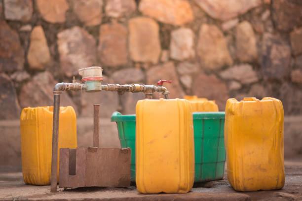 jerrycans and buckets next to a tap to collect water in nyamirambo, a semi-rural part of kigali, rwanda - tap water zdjęcia i obrazy z banku zdjęć