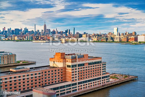 Jersey City waterfront with a Hyatt Regency Hotel and the skyline of New York City USA at sunset.
