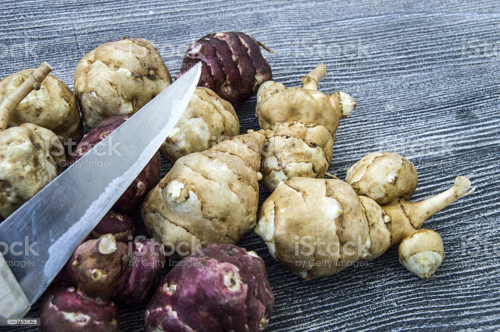 Jerusalem artichoke, cut with a knife on a wooden floor in the next plate and ready to eat, Jerusalem artichoke, in the plate stock photo