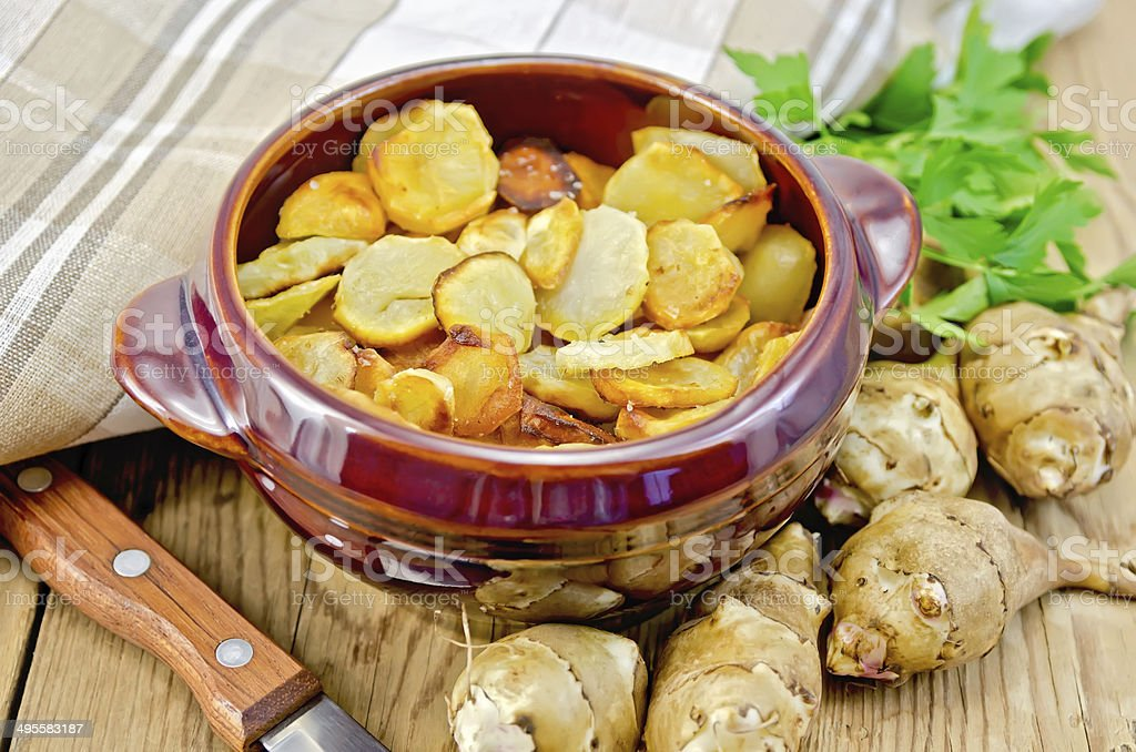 Jerusalem artichokes fried with parsley in pottery stock photo