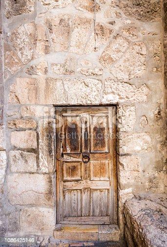 Ancient wooden door and stone walls in Jerusalem, Israel.