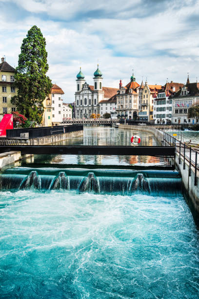 jesuit church and reuss river in old town lucerne, switzerland - lucerne stock pictures, royalty-free photos & images