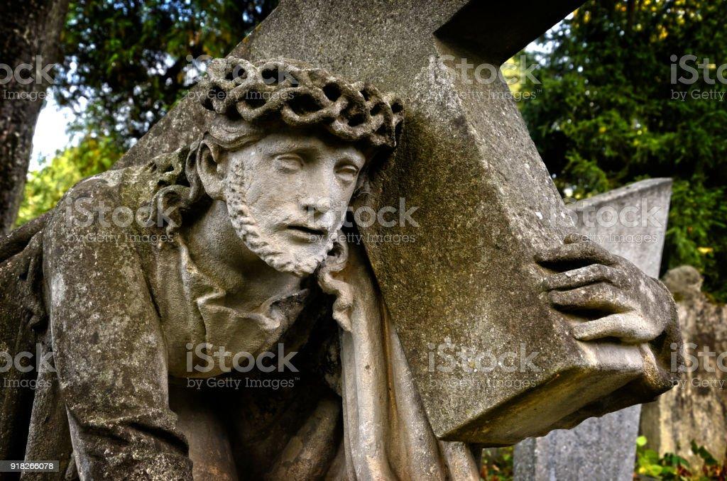 Jesus bearing the cross. Stone sculpture. stock photo