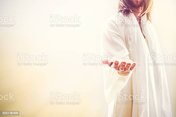 A representation of Jesus Christ following the resurrection in a heaven like setting, extending his hand with the invitation of new life.  His face is obscured, and bright golden light shines around him. A fitting image for Christ rising from the dead as celebrated on Easter Sunday. Horizontal image with copy space.