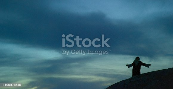 Jesus Christ in Silhouette Prays with Arms Out Outdoors at Sunrise/Sunset under a Dramatic Cloudscape
