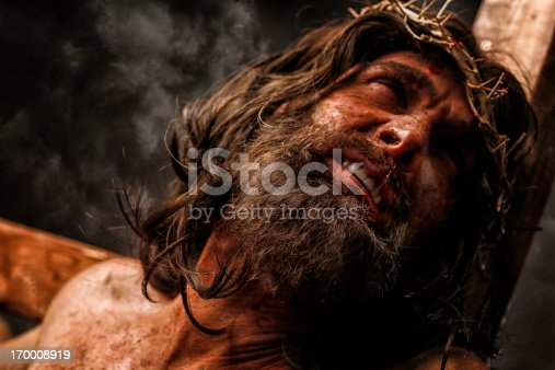 Jesus Christ on cross in pain. This stock image has a horizontal composition.