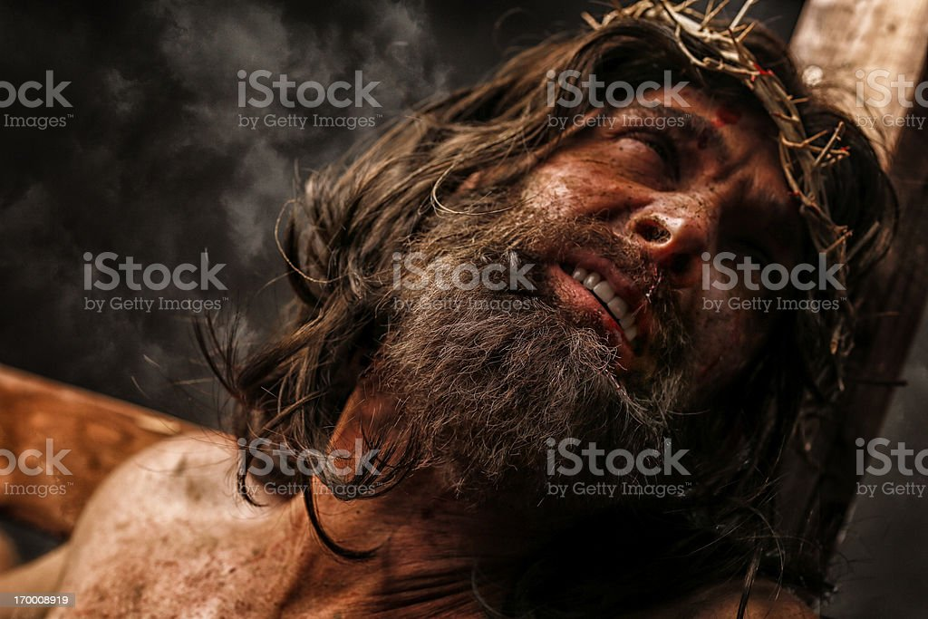 Jesus Christ on cross in pain stock photo