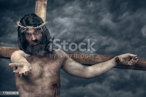 Jesus Christ on cross reach out. This stock image has a horizontal composition.