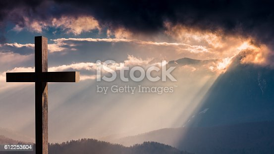 istock Jesus Christ wooden cross on a dramatic, colorful sunset 612253604