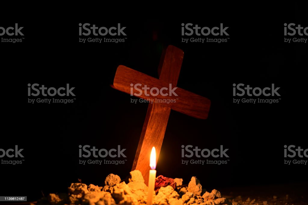 Burning candle under Jesus cross in a cemetery against black...