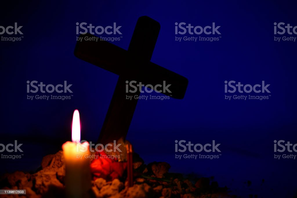 Candle and rose under Jesus cross in a cemetery.