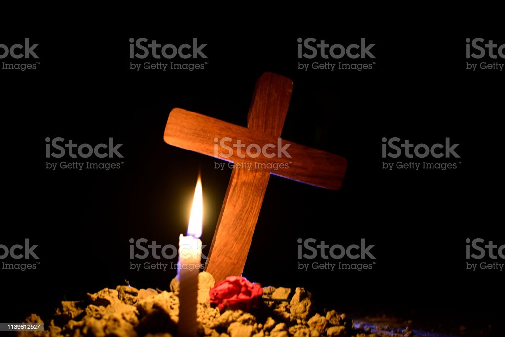 Candle and rose under Jesus cross in a cemetery against black...