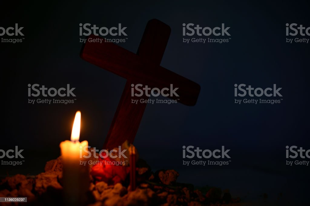 Giving respect to human soul. Burning candle and rose under Jesus...