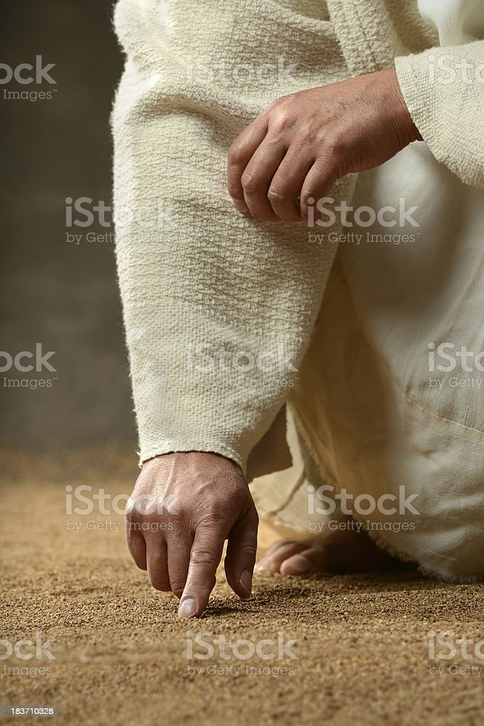 Jesus Finger Writing in the Sand stock photo