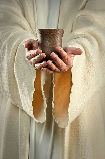 Jesus in white robes holding a pottery cup stock photo