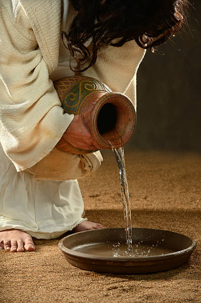 Jesus Pouring Water into Container stock photo