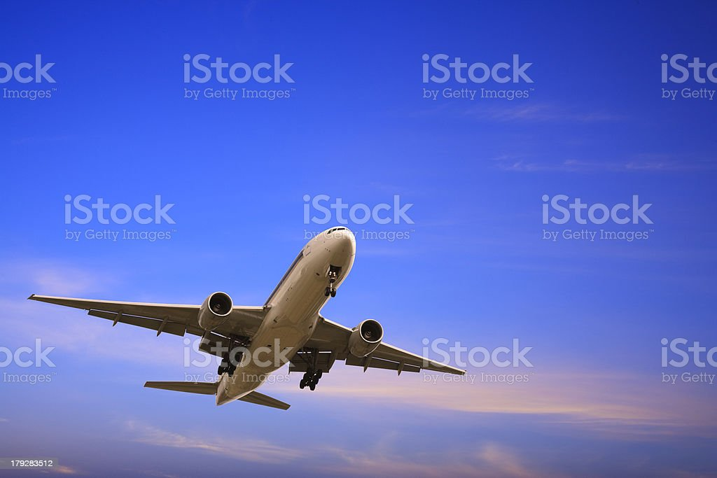 Jet Aeroplane Landing From Bright Blue Twilight Sky Copy Space stock photo