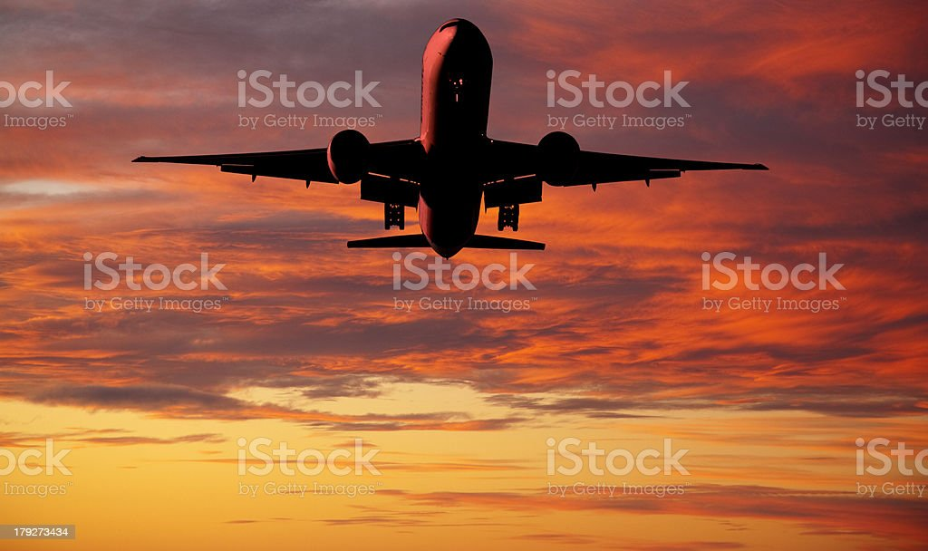 Jet Aeroplane Landing From Bright Red Orange Sunset Sky stock photo
