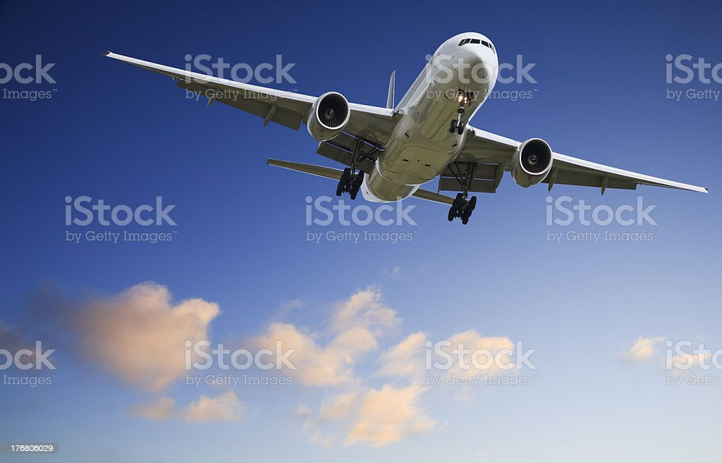 Jet Aeroplane Landing from Bright Sunset Sky Blue Orange Horizon stock photo