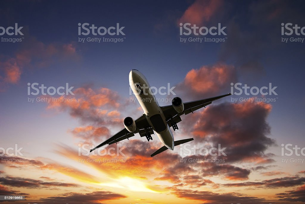 Jet Aeroplane Landing From Bright Sunset Sky stock photo