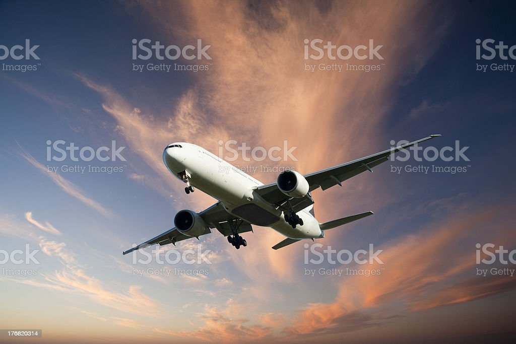Jet Aeroplane Landing from Bright Twilight Sky stock photo