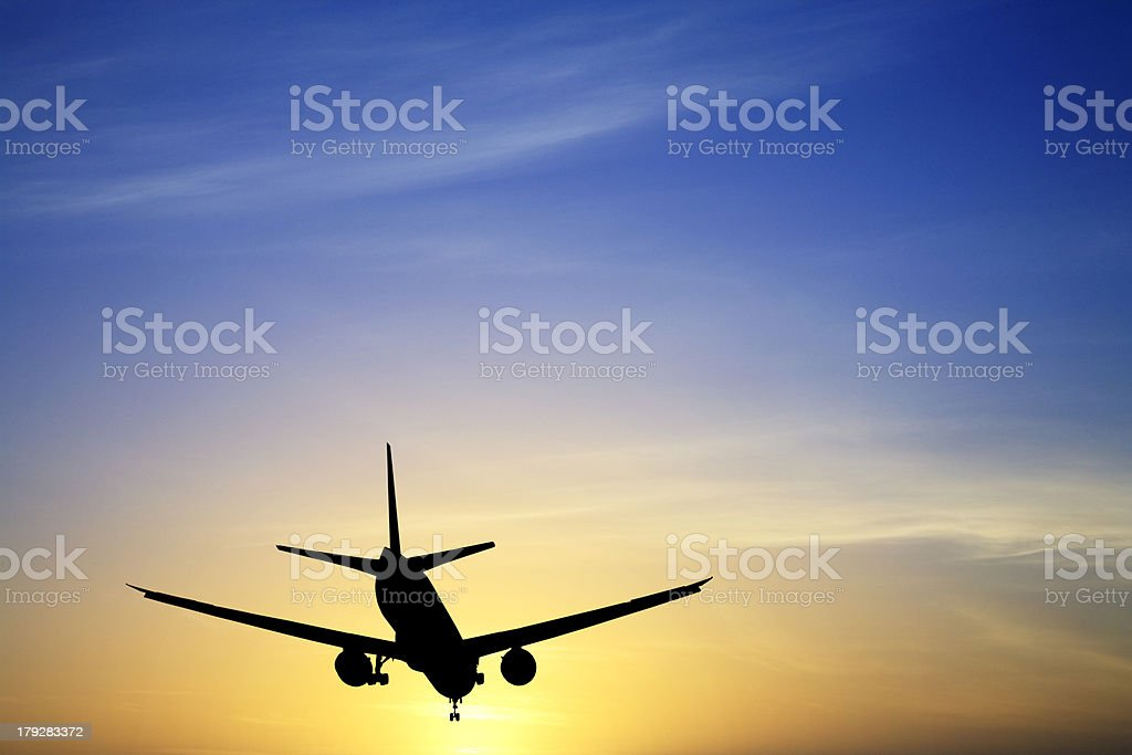 Jet Aeroplane Silhouette Landing at Sunset Blue Yellow Copy Space stock photo