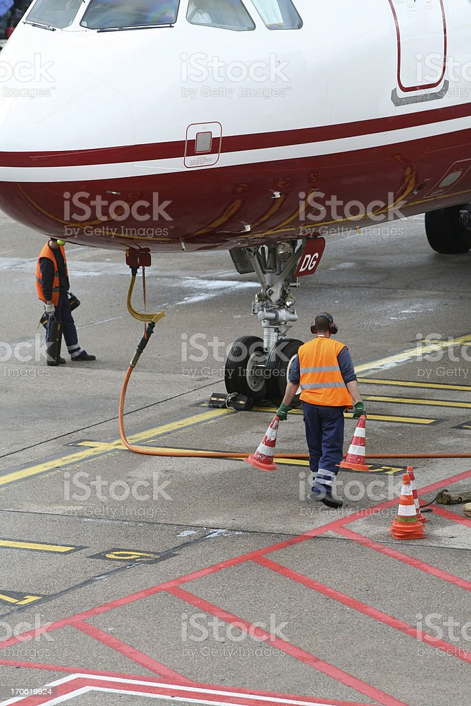jet aircraft at airport, service crew beyond the cockppit stock photo