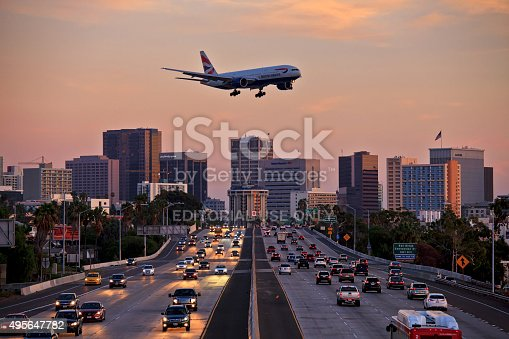 istock Jet aircraft on landing approach flying low over city freeway 495647782
