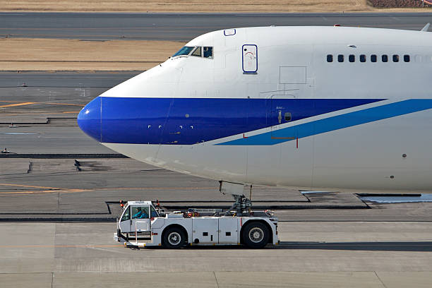 Jet airliner and pulling truck stock photo