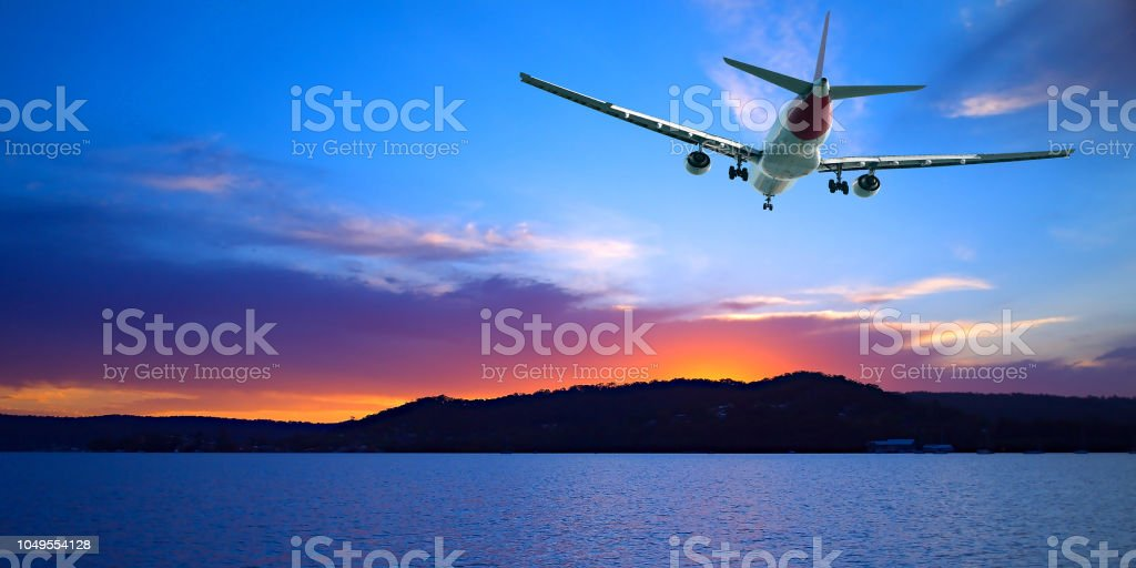 Jet Airliner Flying in a crimson and blue coloured sunset sky. stock photo