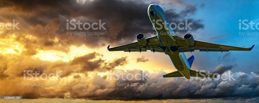 Jet Airliner Flying in a yellow coloured cumulus cloudy sky. stock photo