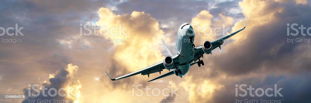 Jet Airliner Flying in an golden coloured cumulus cloudy sky. stock photo