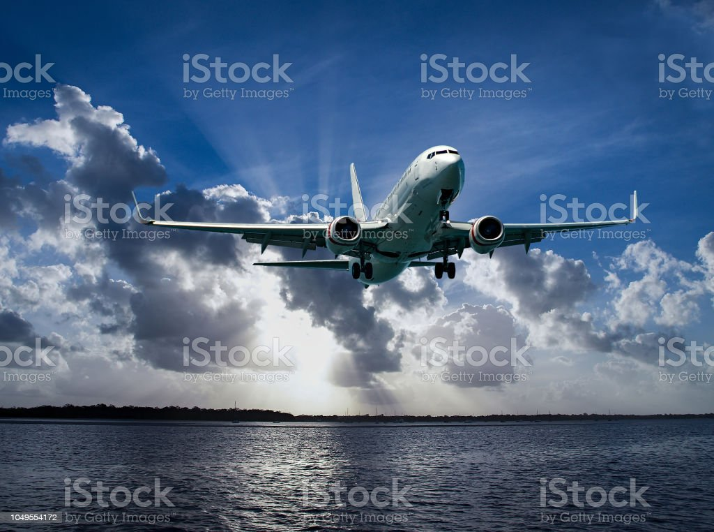 Jet Airliner Flying in subeams and cumulonimbus cloudy sky. stock photo