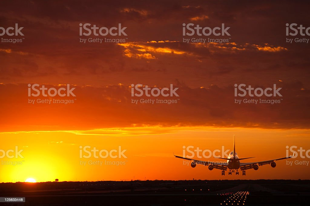 A jet airplane comes in for a landing at sunset stock photo