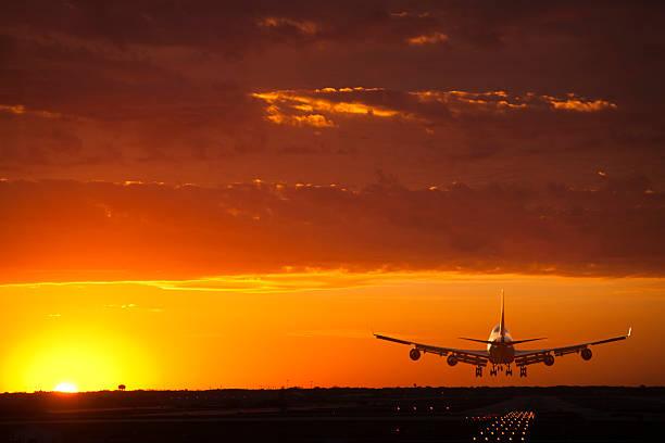 un avión reactor están en un landing at sunset - aterrizar fotografías e imágenes de stock