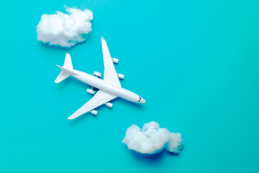 Jet airplane flying between the clouds, minimal concept, on blue background. Minimal transportation, travel or vacation concept